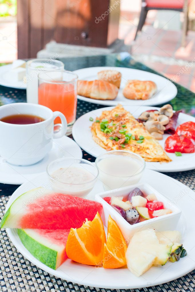 Delicious breakfast of fresh fruits, omelette, grilled tomato and assortment of pastry — Stock Photo #11047612