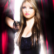 Female performer behind the stage curtain light - Stock Photo