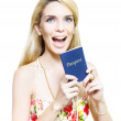 Excited woman clutching a passport - Stock Photo