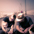 Young couple and baby boy sitting on the boardwalk — Stock Photo