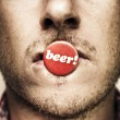 Face Of A Man With Beer Badge - Stock Photo