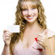 Upbeat beautiful woman with business card — Stock Photo