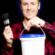 DIY home owner holding up paint and a paintbrush - Stock Photo