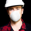 Serious young male artisan wearing protective mask - Stock Photo
