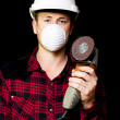 Metal fabrication workman with rotary disc sander - Stock Photo