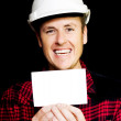 Cheerful laughing builder advertising blank card — Stock Photo