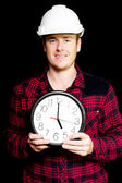 Builder with clock showing home time — Stock Photo