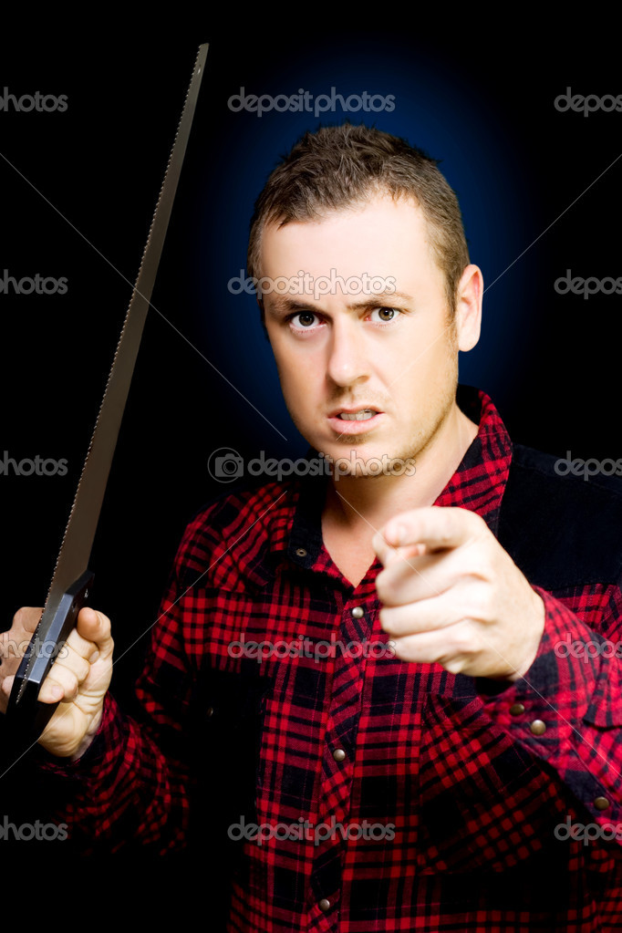 Angry workman with a wood saw in hand pointing an accusatory finger at the camera as he snarls in frustation, conceptual of anger in the workplace, studio portrait on black  Stock Photo #11989149