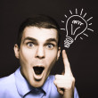 Business man pointing to light bulb illustration - Stock Photo