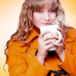 Woman in warm winter coat sipping hot coffee — Stock Photo
