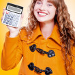 Woman grinning with glee holding calculator — Stok fotoğraf