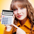 Woman pointing to calculator keypad - Stock Photo