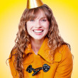 Laughing winter party girl on yellow background - Stockfoto