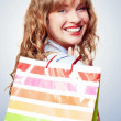 Happy female retail shopper with bag and smile — Stok fotoğraf