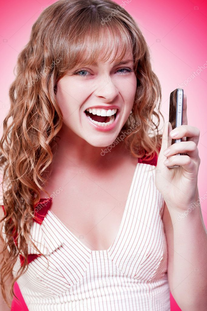 Business woman throwing a temper tantrum as she expresses her displeasure with news that she has just received over her mobile phone on a pink studio background — Stock Photo #12160225