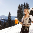 Sexy woman in snow and mountains serving beer — Stock Photo