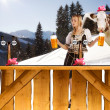 Sexy woman in snow and mountains serving beer — Stock Photo #11621401