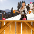 Sexy woman in snow and mountains serving beer — Stock Photo #11621474