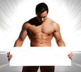 Beautiful and sexy naked man is holding and displaying a white b — Stock Photo