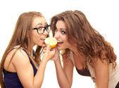 Girls bite a lemon — Stock Photo