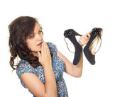 Girl surprised on shoes in his hands — Stockfoto