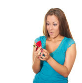 Attractive young woman in blue blouse opens a present and is su — Stock Photo