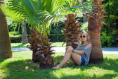 Girl under a palm tree — Stock Photo