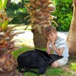 Boy with netbook under palm tree — Stock Photo #11199614
