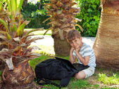Boy with a netbook under a palm tree — Stock Photo