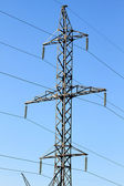 Wide angle view of electricity pylon against blue cloudy sky — Stock Photo