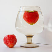 Strawberries in a glass of water — Stock Photo