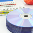 Royalty-Free Stock Photo: Compact discs, color paper, copybook, apple on white desk