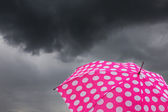 Umbrella with dark clouds — Stock fotografie