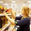 Young woman in the supermarket reading inscription — Stock Photo #11915235