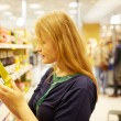 Young woman in the supermarket reading inscription — Stock Photo #11915250