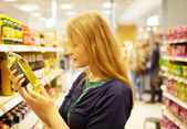 Young woman in the supermarket reading inscription — Stockfoto