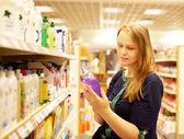 Jonge vrouw in de supermarkt lezen inscriptie — Stockfoto