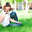 Young girl sitting on grass — Stock Photo