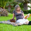 Pregnant woman relaxing in a park reading a book — Stock Photo