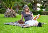Hamile kadın rahatlatıcı bir parkta bir kitap okuma — Stok fotoğraf
