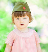 Cute little girl in a soldier's caps — Stock Photo