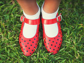 Red shoes with polka dots on a background of grass — Stock Photo