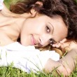 Portrait of beautiful female model laying in the grass — Stock Photo