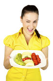 Blinking girl with fresh fruit — Stock Photo