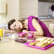 Stock Photo: Woman asleep on kitchen table during breakfast