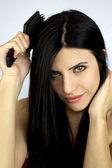 Hermosa chica cepillarse el pelo largo y negro — Foto de Stock