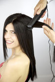 Female model getting long hair ironed — Stock Photo