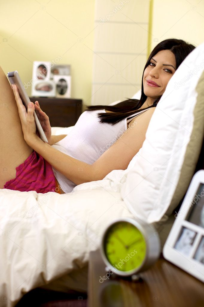 Sensual femal model in her bed in the bedroom smiling with tablet ipad in her lap  Stock Photo #12157044