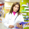 Serious female doctor in pharmacy with documents in her hand — Stock Photo