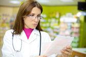 Female doctor reading prescription in pharmacy — Stock Photo